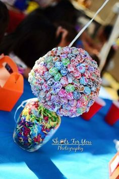 Centerpieces for the party! Glass jars (from dollar tree) filled with confetti papers and dum dum balls poked into a styrofoam ball