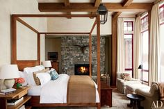 In the master bedroom of a Montana retreat by designer Michael S. Smith, Nancy Koltes bed linens make an inviting statement on a custom-made walnut four-poster by Smith. The ceiling lantern, armchairs, ottoman, and curtain fabric are all by Jasper, as is the dahlia print used for the chairs' pillows.