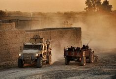 The sun sets as ISAF troops in a Navistar Defense Husky MXT pass Afghan locals on Route Trident in Helmand, Afghanistan.