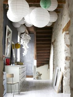 paper lanterns in a hallway with a distresed brick wall
