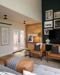 Glass schoolhouse lights, camel leather chairs with wood wall and green wall. LOVE! #livingroomideas