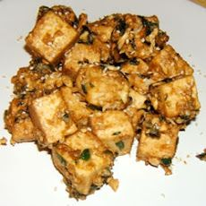 Amazing Simple Thai Tofu 14 ozs firm tofu (cut into 3/4 inch cubes) 1/3 cup green onions (chopped) 11/2 tsps olive oil 1/2 tsp sesame oil 1 tsp soy sauce 2 tsps fresh ginger root (grated) 1/4 cup chunky peanut butter 3 tbsps flaked coconut sesame seeds