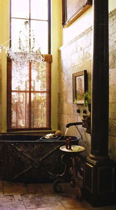 Rustic french country bathroom .,.. love the mix of battered copper tub and crystal chandelier.