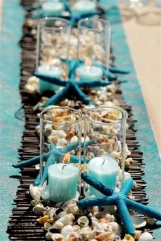 Beach inspired wedding reception table decor idea with shells, starfish and aqua table runner with candles
