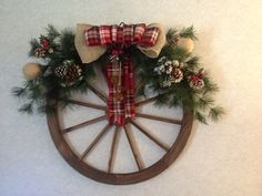 Western wagon wheel Christmas or winter wreath, with greenery, burlap and wire…