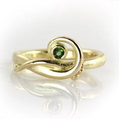 Elegant gold curl ring with green tourmaline. The glittering facets of the juicy green gem creates a beautiful contrast to the glow of the gently undulating gold. Raw meets affectionately smooth, accompanied by happy bubbles