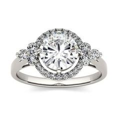 The perfect ring for the perfect bride. This classic Forever One moissanite engagement ring amazes. A single Round cut moissanite stones rests in four prongs, surrounded by a ring of accent stones. A trio of gleaming moissanite stones lay on each side of Beautiful Diamond Rings, Brilliant Diamond, Wholesale Diamond Rings, Forever One Moissanite, Earring Backs, Personalized Jewelry, Halo, Gold Rings, White Gold