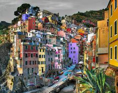 So much color, so old world and staggeringly beautiful and scenic. This looks like Venice in Italy, but it is Riomaggiore, Italy in the province of Le Spezia.    I think the photo's colors might have been enhanced a bit as I've seen a raw daytime photo of the same angle and shot of the village. However, the enhanced version is not too different from the original. Some of the buildings that are purple here are actually white, but there's still a LOT of color diversity in the candid shot.