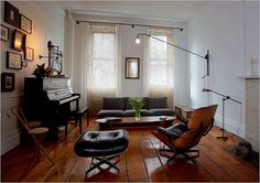 so many things i love about this room..the dream chair, hardwood floors, old piano, gallery wall, industrial lighting..