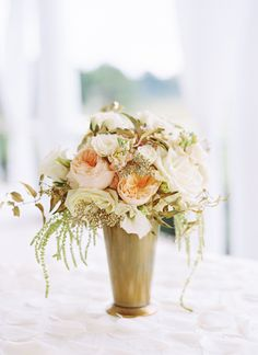a gold mint-julep vase with peach and white flowers make a glamourous centerpiece | Landon Jacob