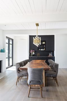 A Jonathan Adler Meurice Rectangular Chandelier hangs from a white plank ceiling over a live edge dining table placed on gray wash floors surrounded by dark gray dining chairs accented with a nailhead trim and complementing a built-in black bar in this ch Gray Dining Chairs, Dining Room Table, Wooden Dining Table Modern, Contemporary Dining Table, Accent Chairs, Elegant Dining Room, Dining Room Design, Traditional Dining Rooms, Live Edge Furniture