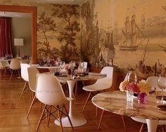 Nos gusta el papel pintado original con barcos que atracan y vinos que se descorchan en la mesa, a la vez.  Fotografía: María Gorbeña