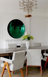 A stunning emerald convex mirror and vintage light fixture, combined with a marble table and modernist chairs.