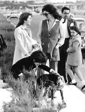 Jacqueline Kennedy Onassis standing with her children and dog.