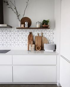 white matte kitchen with wooden chopping boards   open shelf   cube tiles and concrete floor