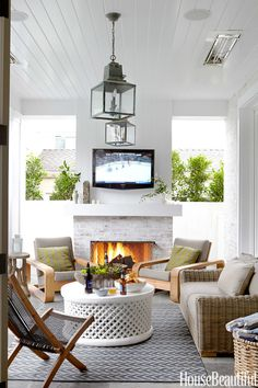 A fireplace and overhead heat lamps make it possible to entertain on the loggia year-round in a Southern California bachelor pad designed by Parrish Chilcoat and Joe Lucas. It's furnished with a Provence love seat in synthetic wicker and St. Barts teak lounge chairs — all from Restoration Hardware — an Ikea Brommö deck chair, a white-painted African table from Berbere World Imports, and Brantley lanterns from Circa Lighting.   - HouseBeautiful.com