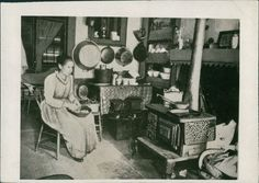 Nice kitchen and stove for the time. Woman peeling potatoes? Great detail