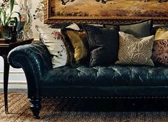 Beautiful leather tufted chesterfield sofa piled with luxurious pillows. THEFULLERVIEW
