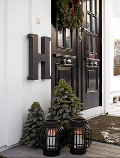 "15 Festive Ways to Decorate Your Front Door via Brit + Co. ""This scene is unfussy, yet everything is perfectly placed. We love how the doubled decor (see two trees and lanterns?) take up space without feeling repetitive, and of course, the monogram letter won us over."""