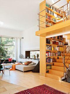 Une maison cube pour les vacances. UN librero que funciona como pared divisoria de las escaleras.