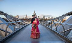 The bride wears a stunning tradtional Indian red dress. The groom wears a Scotish kilt, both look amazing on The Millennium Brodge London.