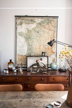 eclectic cabinet display via mademoiselle poirot | retro vintage credenza with an assortment of horns and apothecary bottles | farmhouse rustic dining room table with leather chairs