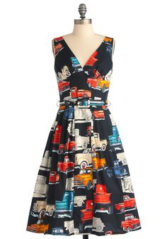 Bygone Days Dress in Cross Country  The StoryDetailsMeasurements  You can't help but be reminded of days gone by when you don this vintage-inspired dress. Featuring a colorful print of vintage trucks against a coal-colored background, this V-neck frock will inspire you to hit the open road. Wrap the removable belt around the banded waist and pair this tea-length dress with cherry-red heels, a vintage necklace, and a stack of golden bangles for a retro-inspired look that's undeniably modern.