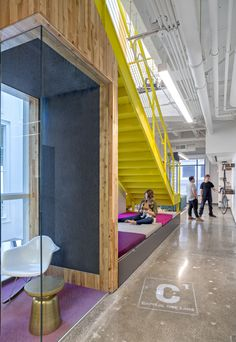 A vibrant yellow staircase, sculptural bike racks, denim walls, and concrete floors accented with fuschia carpeting make this a beautiful and functional space for creative work.