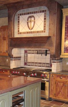 Hand painted and custom tile range hood. Wolf range. Home built by Martin Bros. Contracting, Inc., Goshen, Indiana