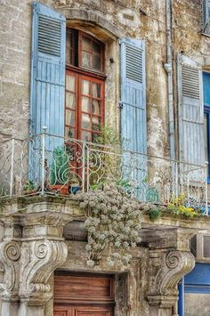 Charming old balcony window adorned with flower pots &  pale blue shutters