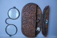 """eyeglass case and nose spectacles dated """"1558"""" on the top. E Cl 21.030. Carved wood, brass hinges. Two people are carved on the front while on the back a man is holding open the mouth of a lion, and there are symbols (weapons) of a Cardinal so the front and the back. This is the oldest know eyeglass case with an actual date on it. Glasses look like silver, frame is an unusual form with lateral slots for lens insertion. May not be original, as they have soldering and screws, so may be early…"""