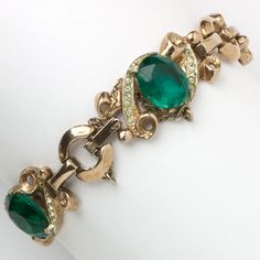 This 1940s Retro Modern bracelet of emerald rhinestones with pavé accents set in rose gold-plated sterling silver is an Adolph Katz design for Corocraft.