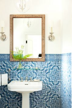 Blue and white bathroom with framed mirror