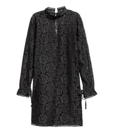 Black. Short, straight-cut lace dress. V-neck opening at back with tie at back of neck, stand-up collar, narrow shoulder straps, and long sleeves with