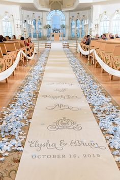 """""""And they lived happily ever after"""" aisle runner with light blue rose petals at Disney's Wedding Pavilion"""