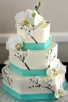 Three hexagon shaped tiers in white fondant are adorned with thick Tiffany Blue ribbon details. A lovely chocolate brown, white, and sky blue cherry blossom design cascades down the sides of the wedding cake, finished with real white orchids.                            I would do this and change the color to coral.