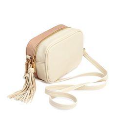 Kleine Schultertasche aus Lederimitat mit einer glatten und einer gemaserten Seite. Die Tasche hat eine Zierquaste an einer Seite, einen Reißverschluss und einen abnehmbaren Schulterriemen. Gefüttert. Größe 7,5x12x19 cm.