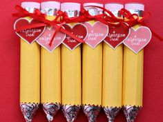 """valentine favor… not exactly sure how these were made, but seems easy enough… hershey kiss on one end, affixed to covered lifesaver roll or rollo chocolate-caramel roll… the eraser end is prepped before the """"pencil"""" is covered in yellow, then tied with the heart-shaped tag.  super cute for school V-party!"""