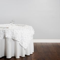 Inspire an air of romance at your special event with white rosette linen. Featuring an intricate, multi-sized rose pattern, a rosette overlay offers an eye-catching, raised texture on an elegant satin fabric. 72 in. square rosette table overlays are perfect for creating a romantic atmosphere at any event, and pair well with floor length tablecloths. Note: Rosette table linens are hand wash only to ensure material integrity.