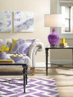A traditional tufted sofa with nailhead trim is brightened with both a yellow and a purple throw pillow. A contemporary purple rug adds graphic punch to the space, while abstract painted canvases bring a soft touch to the walls.