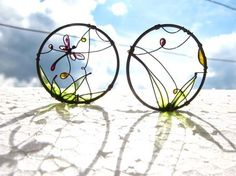 Dragonfly Earrings are copper earrings with a picture of a beautiful sunny summer landscape. A raspberry color dragonfly is flying over the green