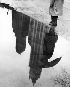 """The Woolworth Building reflected in a puddle in City Hall Park. The original caption, """"an eerie reflection of the skyline."""" Photo: Arthur Brower/The New York Times, April 20, 1950"""