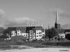 Riesiges Baugrundstück mit Bagger und Erdwällen und dem Kirchturm der Herz-Jesu-Kirche im Hintergrund, aufgenommen in klassischem Schwarzweiß in Münster in Westfalen im Münsterland
