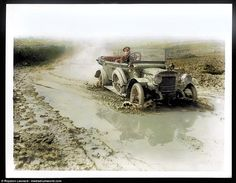A soldier driving a motor car along a muddy and badly flooded road in an unknown location,...