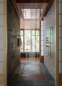 Beautiful rain head shower with natural stone like walls along with lots of wood exposure