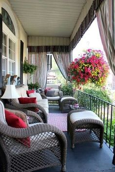 Magnificent porch room: gray wicker furniture, white cushions, red accent pillows, rug, a gorgeous hanging flowering plant, plus space defining outdoor drapes.