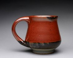 "This handmade pottery mug is glazed with a combination of an iron red and a light green celadon. The ring around the belly was created by the two glazes overlapping. Measures 4"" tall x 5"" wide (10.2 cm x 12.7 cm) at the handle and holds 14 oz. The opening is 3"" wide (7.9 cm). This mug is light weight, and has a comfortable two/three finger handle."