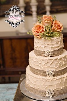 Three tiered rustic wedding cake wrapped in burlap with pearl broaches and flower topper. Country fall wedding.  Photography: www.TheAthensWeddingPhotographer.com Coordinating:  Wild Flower Event Services Venue:  The Thompson House and Gardens Floral:  Flowers by On
