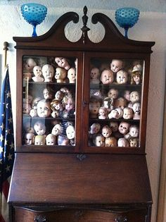 This cracks me up. Collection of old doll heads stuffed into a beautiful antique cabinet.