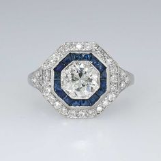Gorgeous 1.66ct t.w. Art Deco Old European Cut Diamond & Sapphire Ring Platinum | Antique & Estate Jewelry | Jewelry Finds Price: $5999.00  Hello, Gorgeous! This massive and glorious art deco diamond and sapphire engagement ring will impress the pickiest of jewelry admirers! The central sparkling old European cut diamond weighs an approximate .94cts and has the quality grade of J-K color, I1 clarity. The ring has a hexagon shape with sparkle, a bit of blue beauty, and an era appropriate…